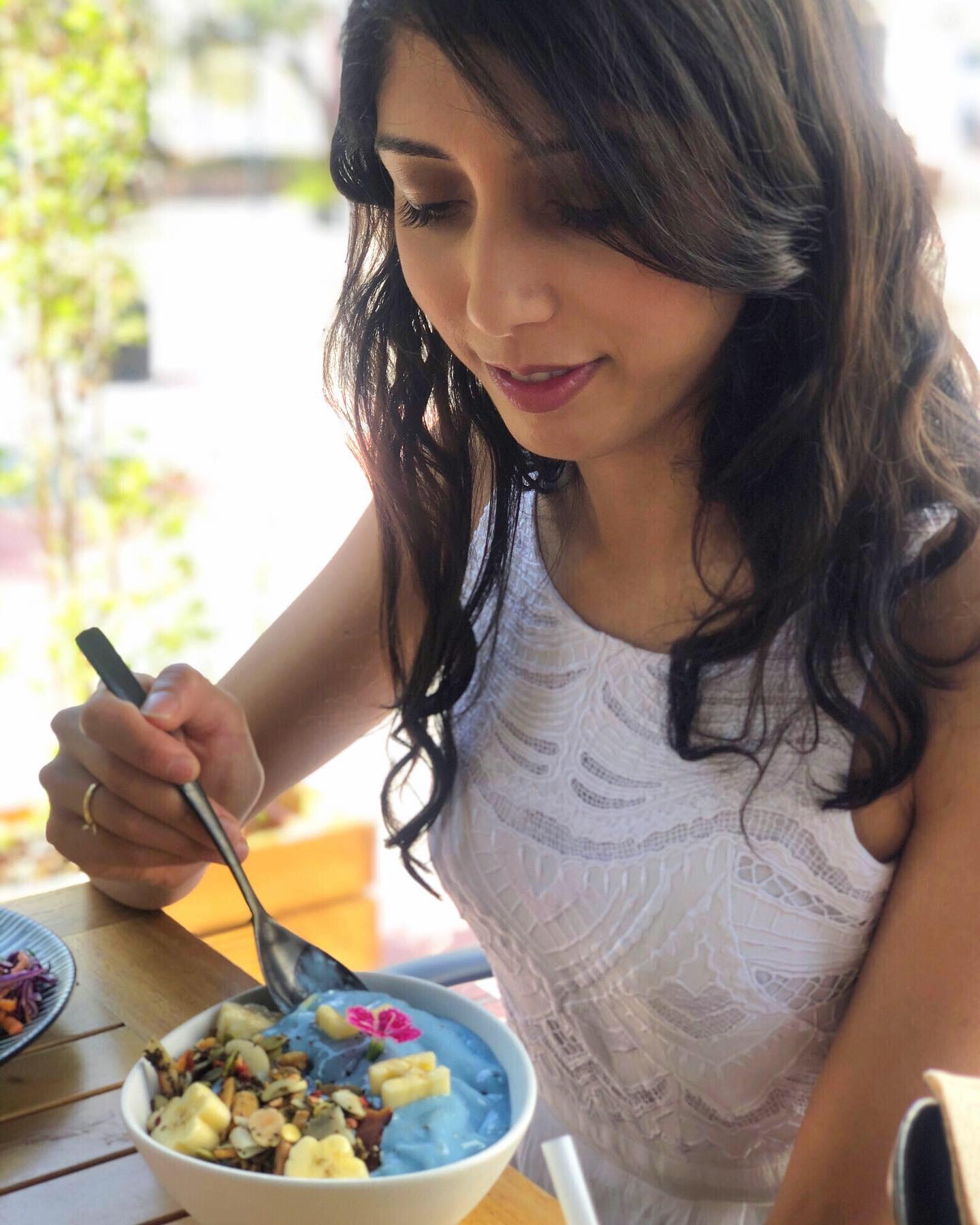 Girl eating vegan spirulina bowl