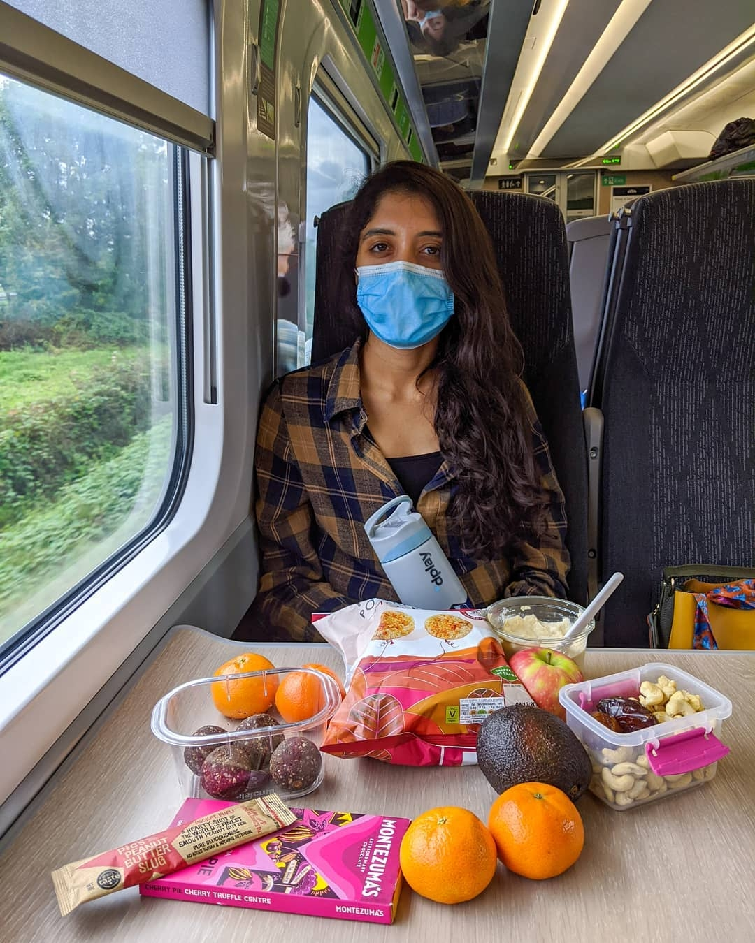 Photo of a girl wearing a mask with fruit and other snacks laid out in front of her