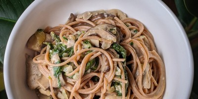 Top down view of white bowl with creamy vegan whole grain spaghetti with mushrooms and greens
