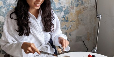 Woman in a white bathrobe eating breakfast