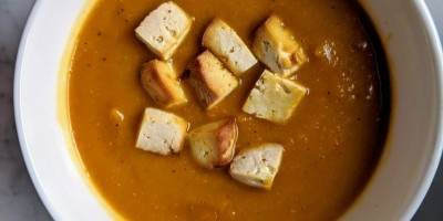 Bowl of butternut squash soup with tofu croutons