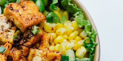 Bowl of marinated tofu with sweetcorn, cucumber and salad leaves
